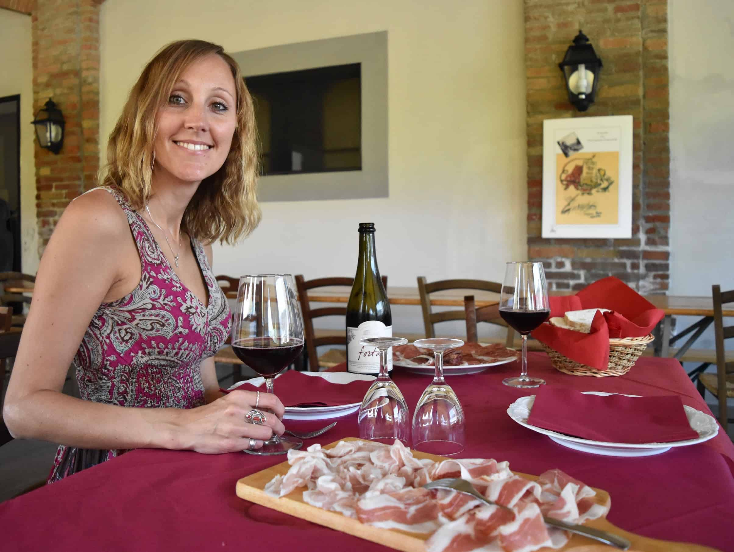 Hayley drinking a glass of lambrusco with a board of salumi